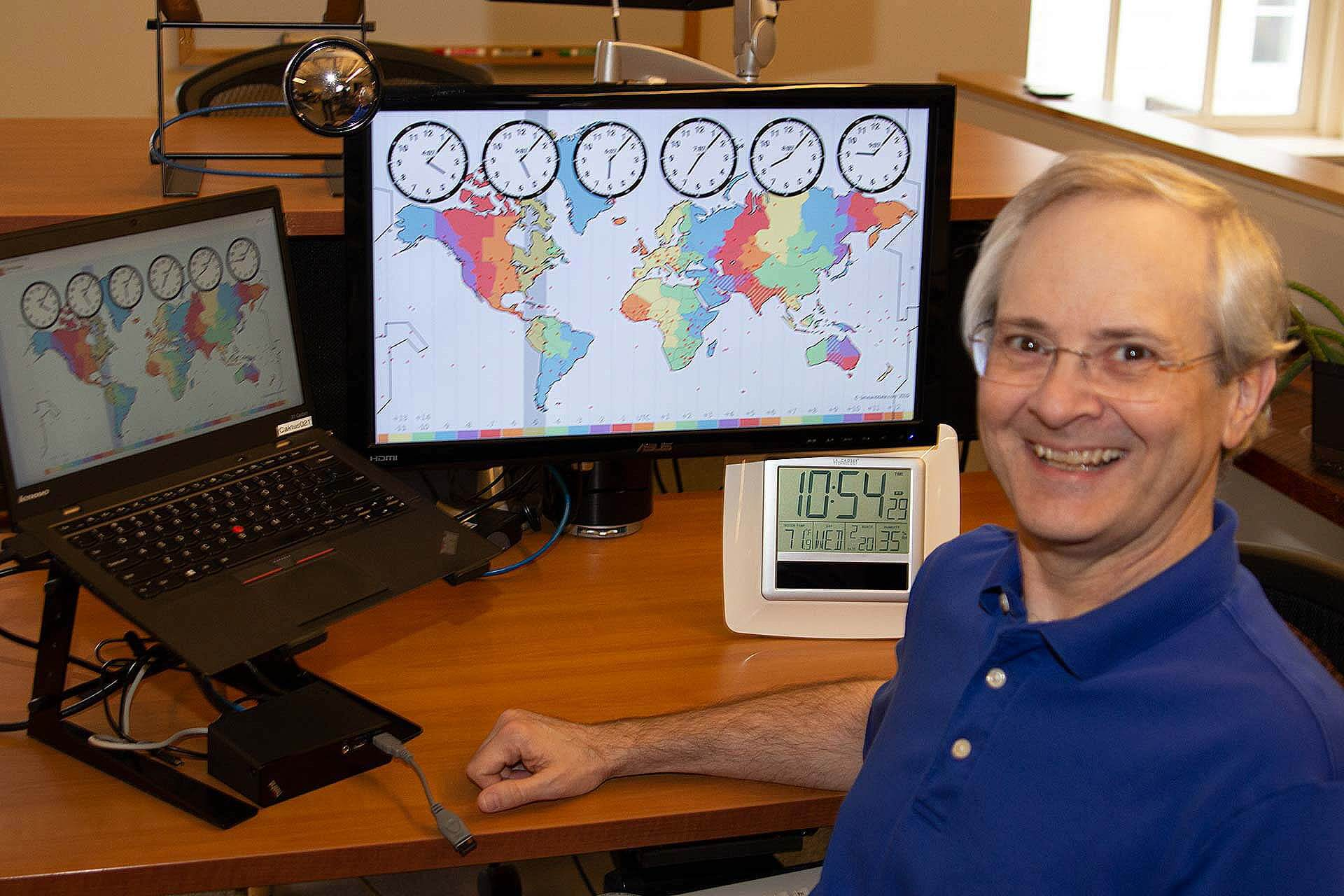 Developer and blog author Dan Poirier at his desk, with a graphic of timezones on his screen.