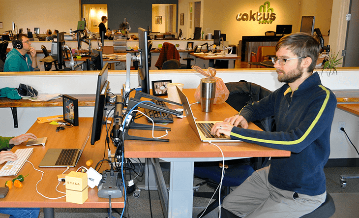 Developer and blog author Dmitriy Chukhin codes at his desk in the Caktus office