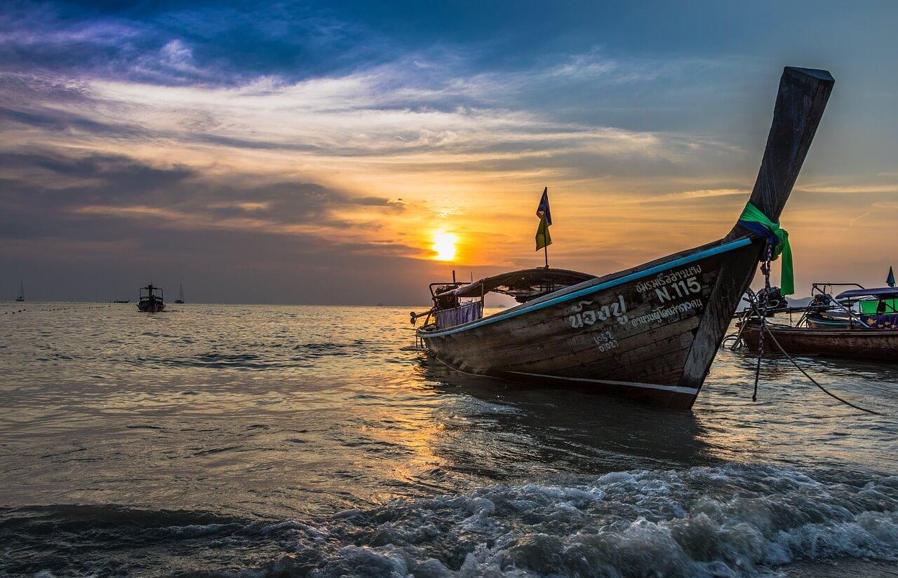 A ship at the shore at sunset.