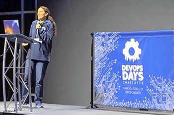 Devopsdays speaker Quintessence Anx on stage, giving her presentation