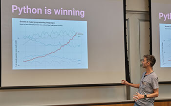 "Tom Dyson in front of a screen that reads ""Python is winning"""