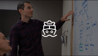 Developers working together and referring to a whiteboard.