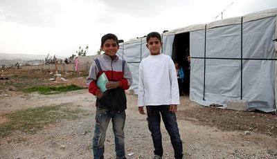 Muhanad and Ahmad*, two Syrian refugee boys outside Ahmad's temporary home, in Lebanon's Bekaa Valley.